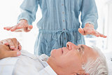 Man receiving Reiki treatment by therapist