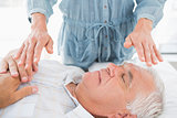 Man having Reiki treatment by therapist