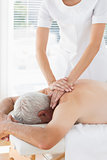 Physiotherapist massaging back of patient