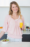 Woman with salad holding orange juice in kitchen