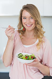 Woman having salad in kitchen