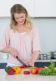 Woman chopping vegetables at kitchen counter