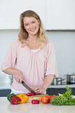 Young woman chopping vegetables at kitchen counter