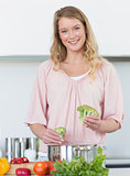 Woman preparing broccoli at kitchen counter