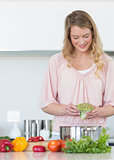 Woman preparing broccoli in kitchen