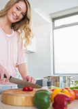 Happy woman chopping vegetables on board