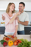 Woman feeding capsicum to man in kitchen