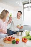 Playful couple preparing food together