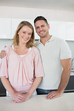 Smiling couple standing at kitchen counter