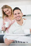 Couple with coffee mugs and newspaper in kitchen