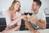 Couple toasting red wine glasses at table