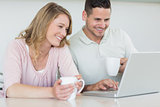 Couple with coffee mugs using laptop at table