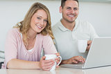Couple with coffee mugs and laptop at table