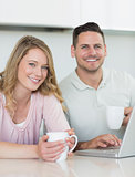 Couple with coffee mugs and laptop sitting at table