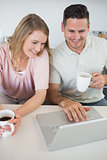 Couple using laptop while holding coffee cups