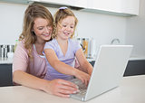 Mother assisting daughter in using laptop at table