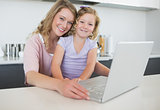 Mother and daughter with laptop at table