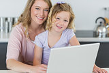 Mother and daughter with laptop in kitchen