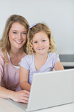 Mother and daughter with laptop at kitchen table