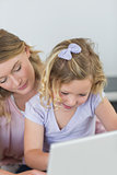Girl using laptop with mother