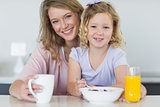 Mother and daughter having breakfast at table