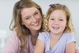 Girl and mother smiling together at home
