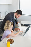 Businessman and daughter using laptop at table