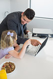 Businessman pointing at laptop while looking at daughter