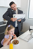 Businessman multi tasking while daughter having breakfast