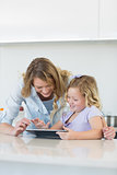 Woman and daughter using digital tablet together