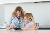 Woman and daughter using tablet computer