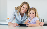 Mother and daughter holding digital tablet at table