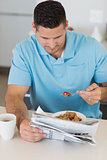 Man reading newspaper while eating breakfast