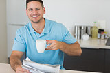 Man with newspaper holding coffee cup at table
