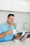 Man with newspaper drinking coffee at table
