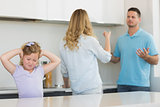 Girl covering ears while parents arguing