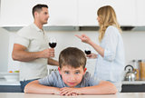 Sad boy leaning on table while parents arguing