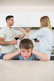 Boy covering ears while parents arguing