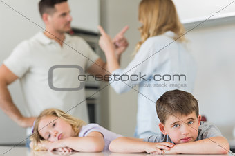 Children leaning on table while parents arguing