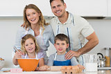 Happy family baking cookies at kitchen counter