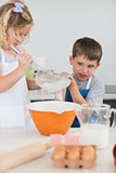Cute children baking cookies in kitchen
