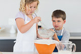 Children preparing cookies in kitchen