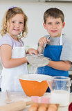 Children baking cookies together in kitchen