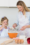 Mother teaching daughter to make cookies