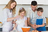 Family making cookies together in kitchen