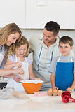 Parents assisting children in baking cookies