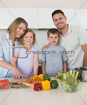 Loving family chopping vegetables in kitchen