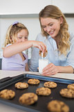 Mother with daughter dipping cookie in milk