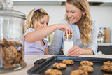 Woman with daughter dipping cookie in milk