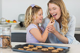 Girl feeding cookie to mother at counter